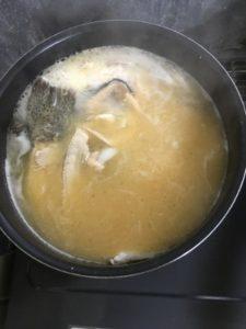 ニジマスのアラ汁に味噌を溶き入れる